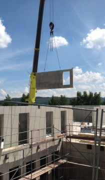 A crane hoists a wall into its new position on the upper floor.