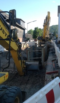 The excavator and its companion in front of our building (on right).